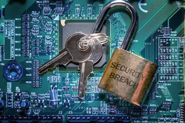 Um cadeado com a inscrição uma violação de segurança e as chaves no pcb. segurança de computador na internet e conceito de proteção de rede.
