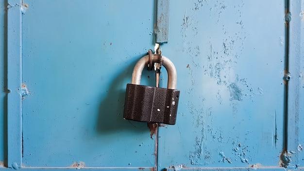 Um cadeado preto em uma porta de garagem de metal azul. fechar-se.
