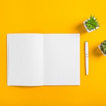 Um caderno aberto com folhas brancas limpas ao lado de uma caneta branca e dois potes de suculentas em um fundo amarelo brilhante