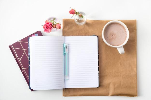 Um caderno aberto com folhas em branco em um desktop branco ao lado de um vaso de rosas e uma xícara de café. vista superior, lay plana