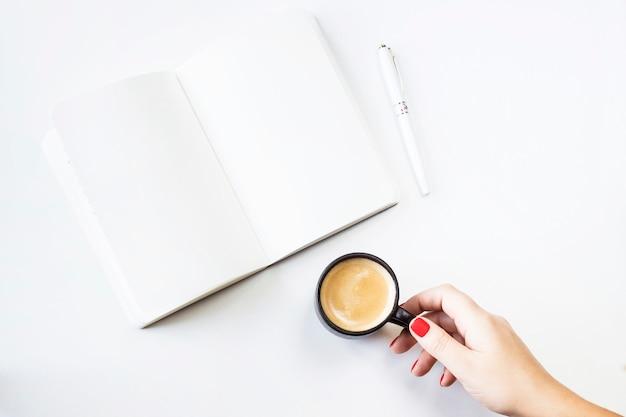 Um caderno aberto com lençóis brancos limpos ao lado de uma caneta branca e uma xícara de café
