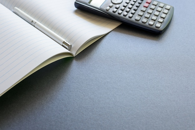 Um caderno aberto com uma pena e uma calculadora, no fundo cinzento escuro, na escola da cena ou no escritório.
