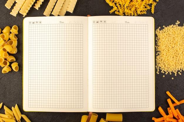 Um caderno aberto de vista superior, juntamente com massas cruas amarelas formadas diferentes, isoladas no fundo escuro refeição comida italia massas