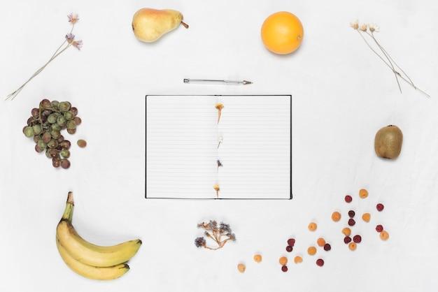 Um, caderno aberto, e, caneta, cercado, com, diferente, frutas, sobre, branca, fundo
