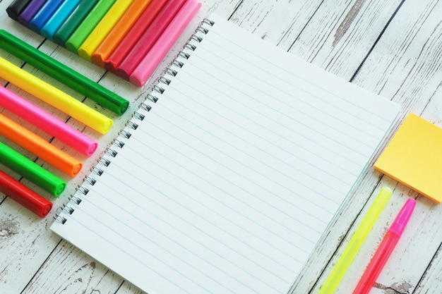Um caderno aberto, marcadores brilhantes coloridos, canetas e argila