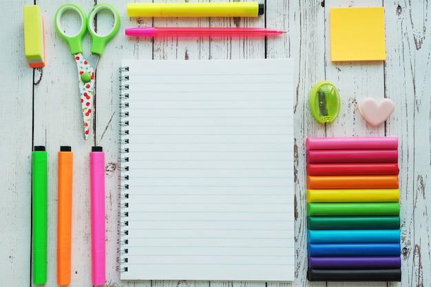 Um caderno aberto, marcadores coloridos brilhantes, canetas, apontador, borracha, tesoura, adesivos e argila