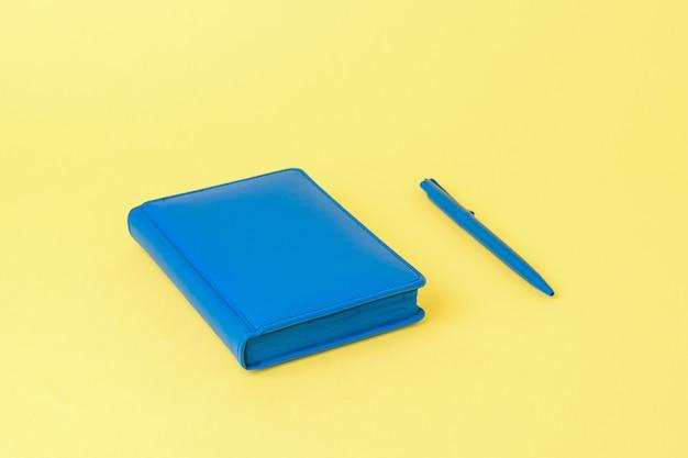 Um caderno azul e uma caneta esferográfica azul em um fundo amarelo. imagem monocromática de acessórios de escritório.