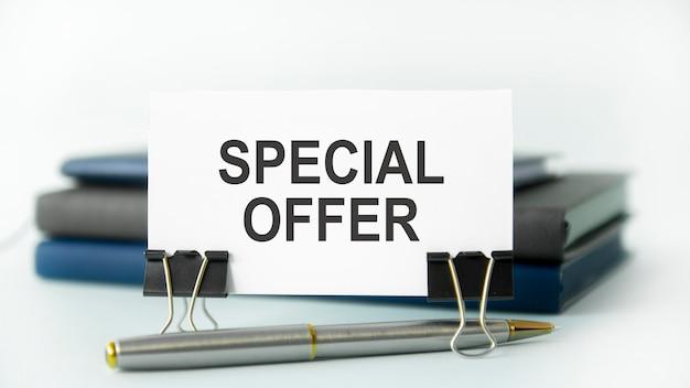 Um caderno branco com o texto oferta especial está em um cartão de papel branco, conceito de negócios