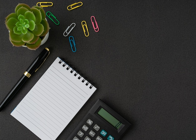 Um caderno, calculadora e caneta em fundo preto com um espaço de cópia. conceito de negócios e finanças. postura plana.