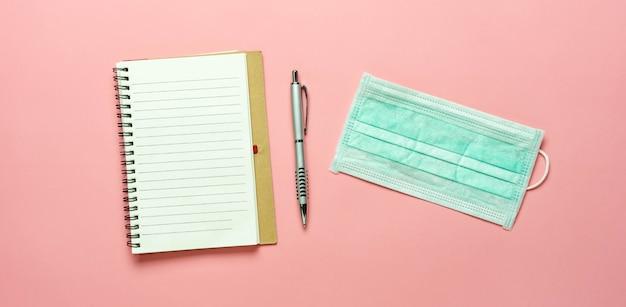 Um caderno, caneta e máscara protetora