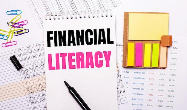 Um caderno com as palavras alfabetização financeira, um marcador, clipes de papel coloridos e papel de anotação brilhante estão no fundo dos gráficos