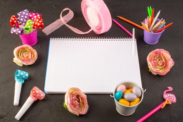 Um caderno com vista de cima e doces junto com flores, velas e lápis na mesa escura.