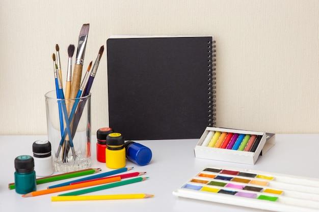 Um caderno de desenho preto em uma mesa branca com suprimentos de desenho e pincéis