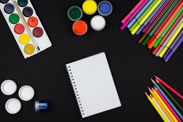 Um caderno e ao lado lápis e tintas em um fundo preto