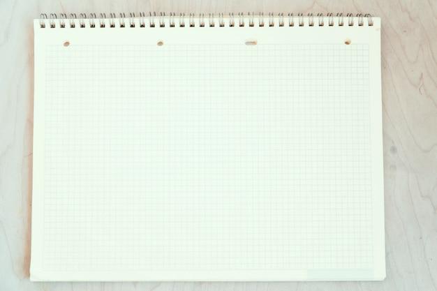 Um caderno em branco aberto, páginas em uma gaiola