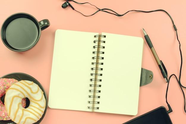 Um caderno nas molas com páginas brancas repousa sobre um fundo rosa.