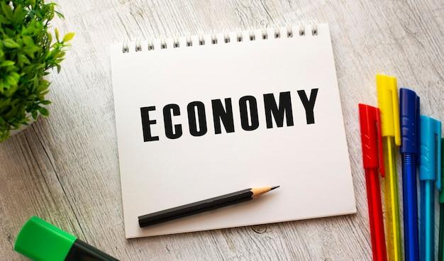 Um caderno sobre uma mola com o texto economia em um lençol branco encontra-se sobre uma mesa de madeira com canetas coloridas. conceito de negócios.
