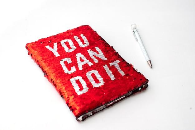 Um caderno vermelho com a inscrição - você pode fazer isso