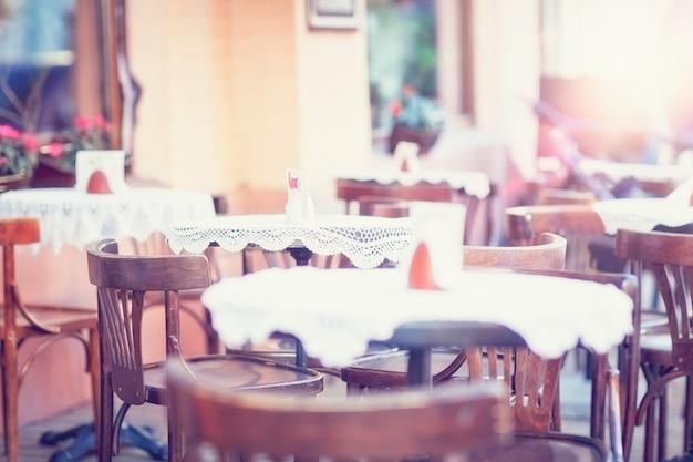 Um café ao ar livre com cadeiras vintage, mesas, toalhas de mesa brancas.