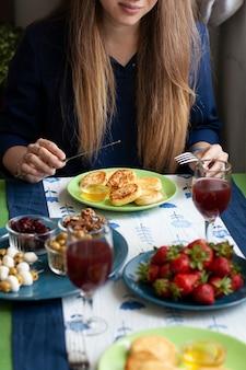 Um café da manhã gourmet para dois: syrnyky, morangos, suco de uva e vários aperitivos.