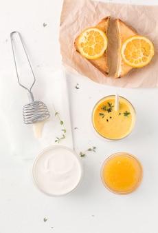 Um café da manhã natural de sanduíches com geléia de laranja e lassi. nas proximidades existem ingredientes de iogurte.