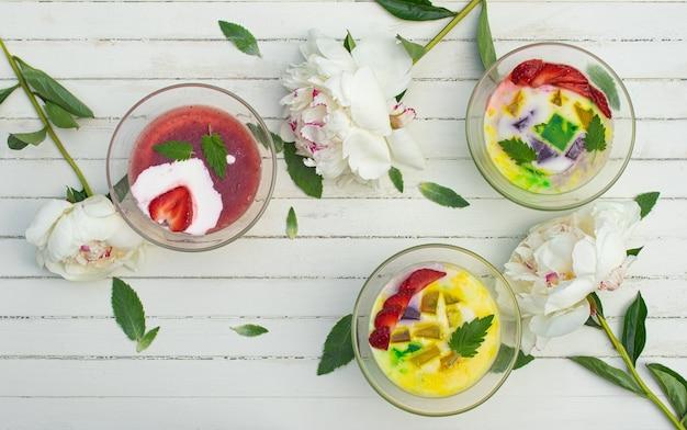 Um café da manhã saudável com geleia de leite com frutas frescas em tigelas de vidro sobre uma mesa rústica