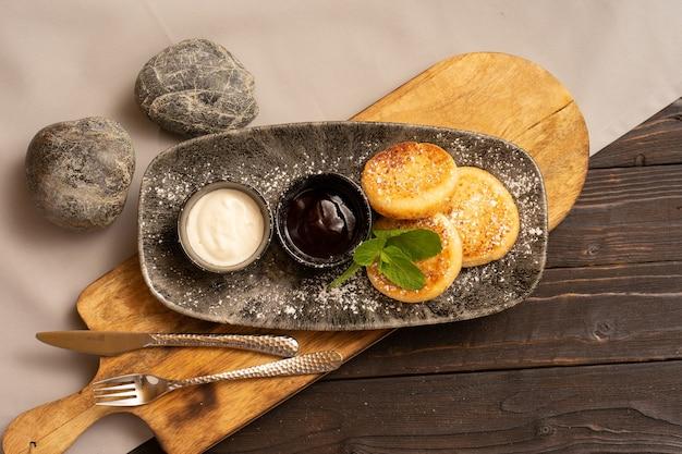 Um café da manhã saudável com requeijão é lindamente servido em uma mesa de madeira, vista de cima.