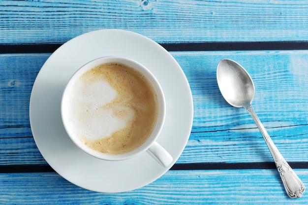 Um café espumoso com cappuccino em uma caneca branca sobre um fundo azul de madeira