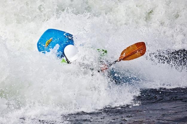 Um caiaque masculino ativo rolando e surfando em águas agitadas