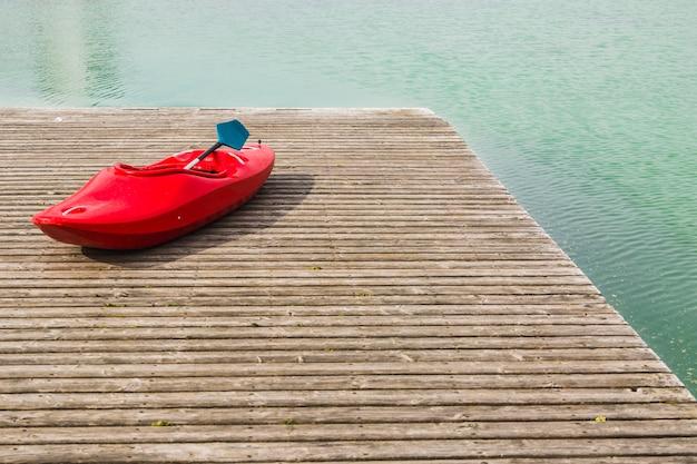 Um caiaque vermelho no cais de madeira em um lago