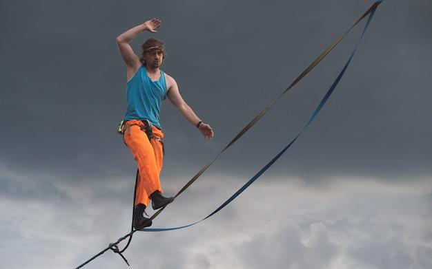 Um caminhante da corda caminha ao longo da linha alta contra o fundo de um céu dramático