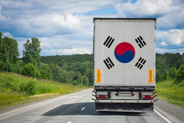 Um caminhão com a bandeira nacional da coréia do sul retratada na porta dos fundos transporta mercadorias para outro país ao longo da estrada.