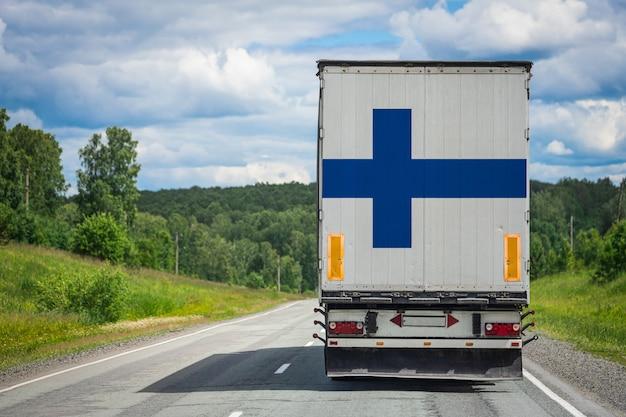 Um caminhão com a bandeira nacional da finlândia, retratada na porta dos fundos, transporta mercadorias para outro país ao longo da estrada.