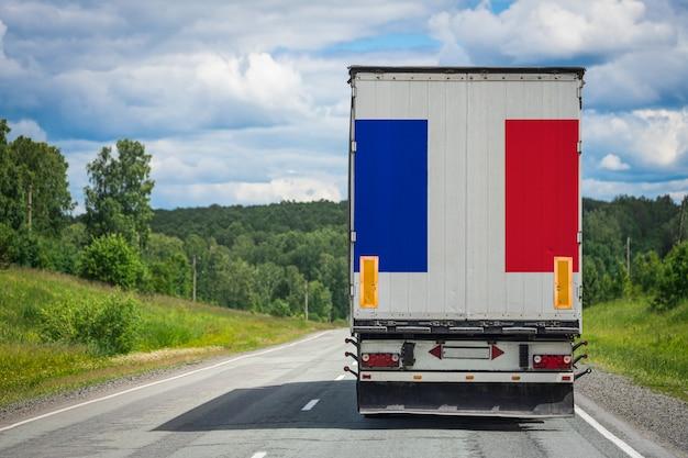 Um caminhão com a bandeira nacional da frança, retratada na porta dos fundos, transporta mercadorias para outro país ao longo da rodovia.
