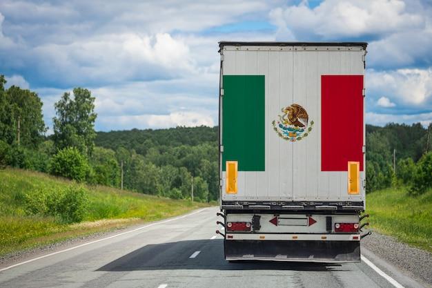 Um caminhão com a bandeira nacional do méxico, retratado na porta dos fundos