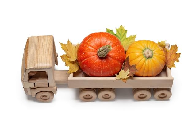 Um caminhão de brinquedo de madeira carrega abóboras e folhas de bordo de outono nas costas.