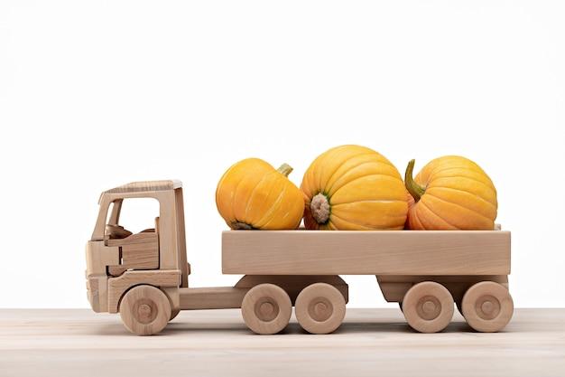 Um caminhão de brinquedo de madeira transporta abóboras maduras. fundo branco, copie o espaço.