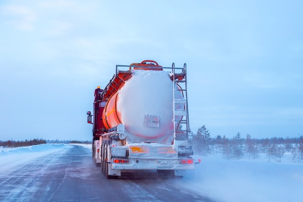 Um caminhão de combustível está dirigindo ao longo de uma estrada no norte no inverno