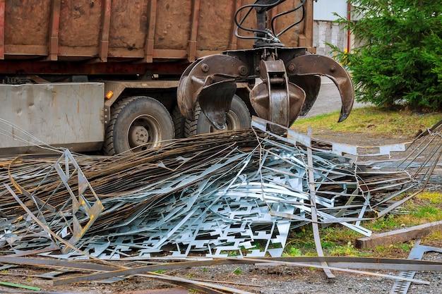 Um caminhão de garra carrega sucata de metal industrial para reciclagem.