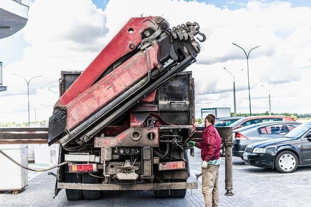 Um caminhão de máquina com um guindaste carregador descarrega blocos para a construção de uma casa.