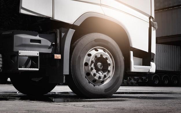 Um caminhão grande tem pneus de caminhão no estacionamento no armazém.