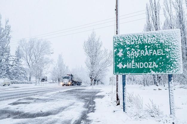 Um caminhão viaja pela estrada de neve durante uma tempestade de neve.