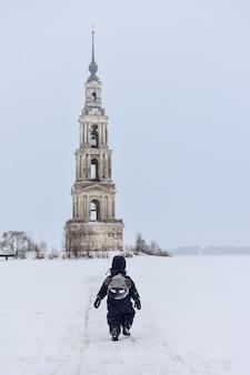 Um campanário no meio de um lago congelado, uma criança andando de costas