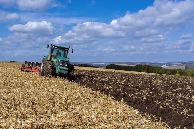 Um campo arado após a colheita de milho com um trator completo com um arado de oito corpos