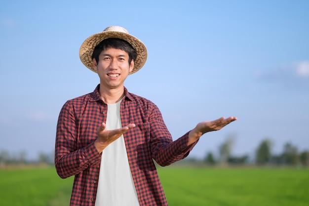 Um camponês com um chapéu trançado está de pé em um campo, posando com as mãos para cima. foco seletivo na imagem do rosto.