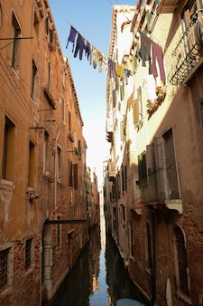 Um canal em veneza, itália, entre prédios antigos com roupas lavadas de moradores penduradas entre eles, fileiras de janelas e varandas