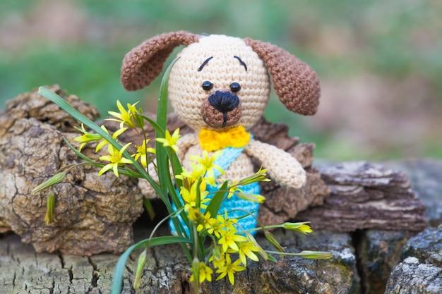 Um cão marrom pequeno em calças azuis. brinquedo de malha, feito à mão, amigurumi