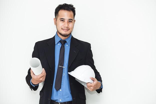Um capacete nas mãos de um jovem engenheiro.