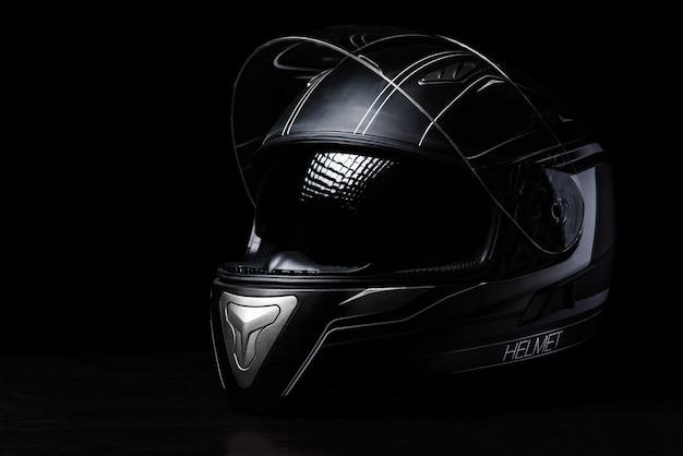 Um capacete preto da motocicleta no fundo escuro.