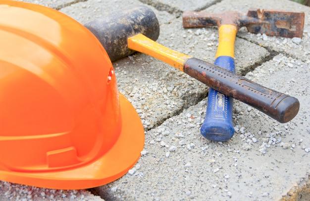 Um capacete protetor laranja e velhos martelos em cinza